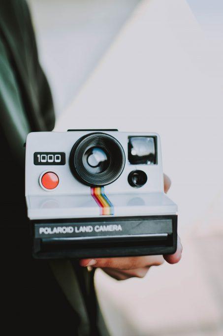 A person holding Polaroid Land Camera