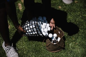 A person pouring golf balls in a brown leather bag
