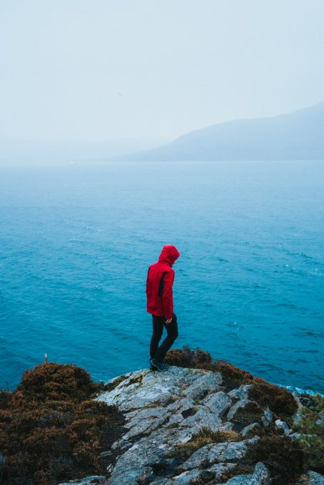 A person wearing a red jacket standing on a cliff by the water