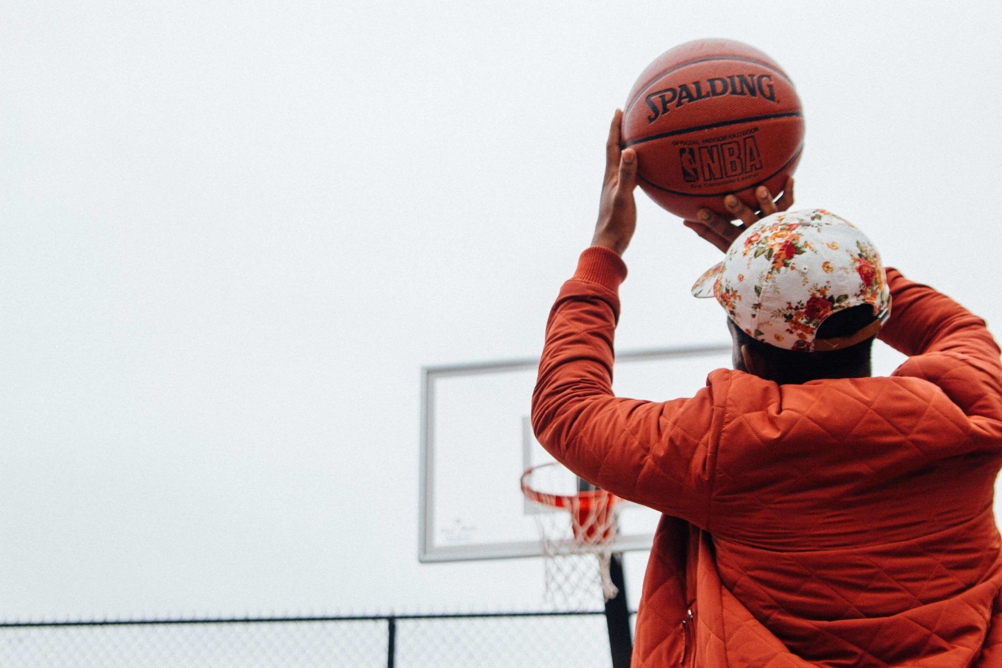 A person wearing an orange jacket and cap holding a basketball