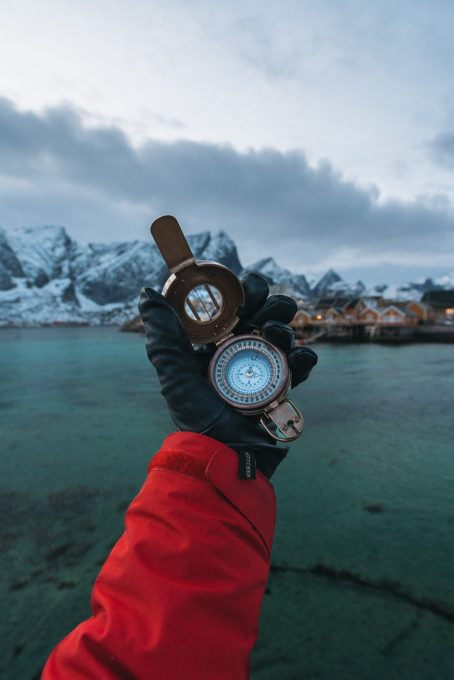 A person wearing leather gloves holding a compass in front of mountains