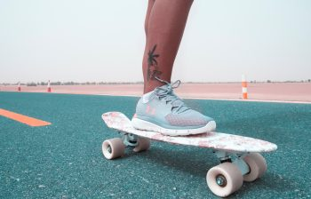 A person with a leg tattoo skateboarding on a road
