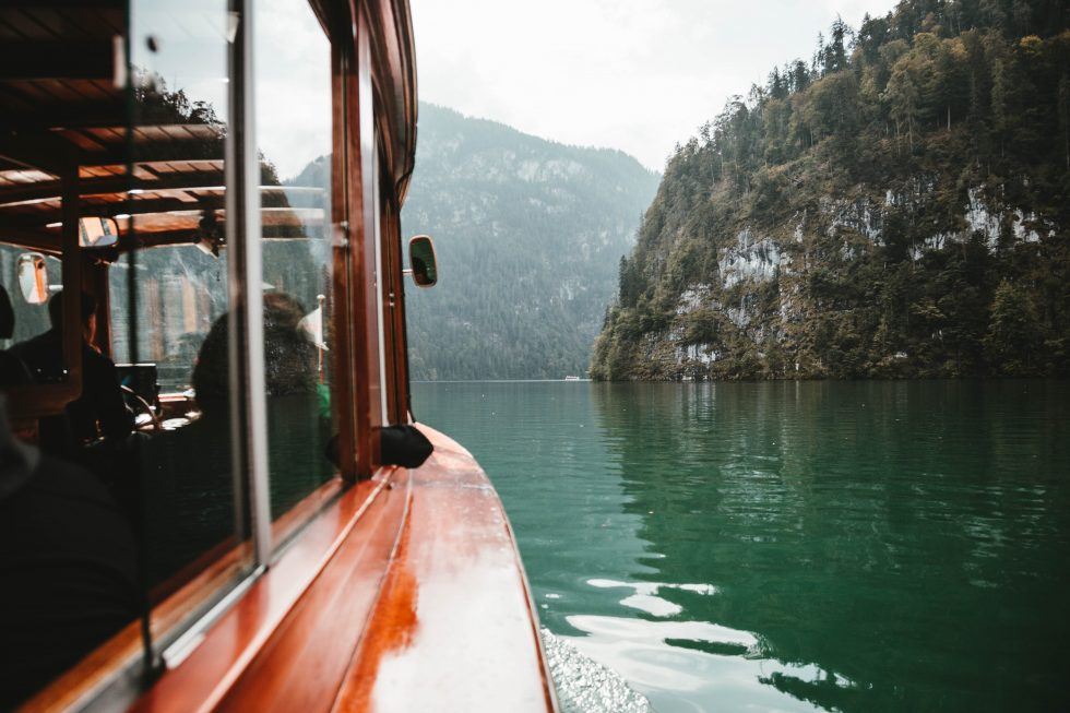A photo from a red boat floating between mountains