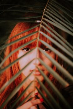 A red-haired woman behind a palm leaf