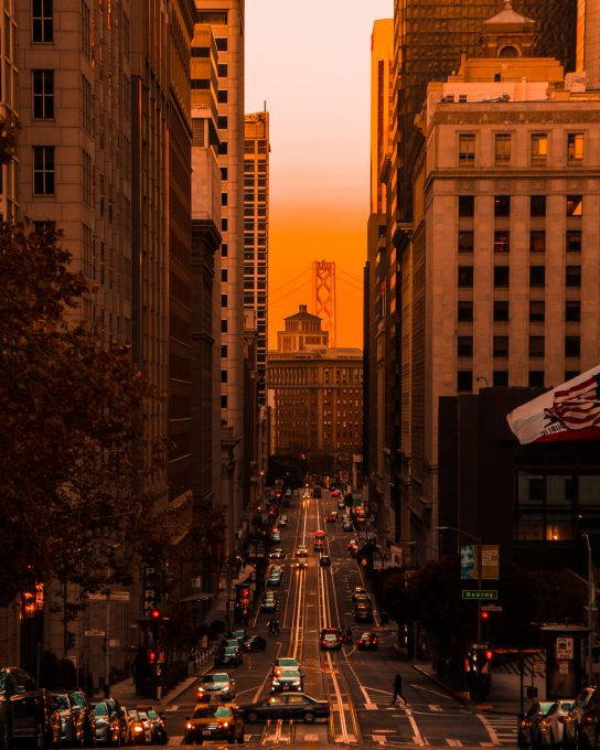 A road between two high-rise buildings during sunset