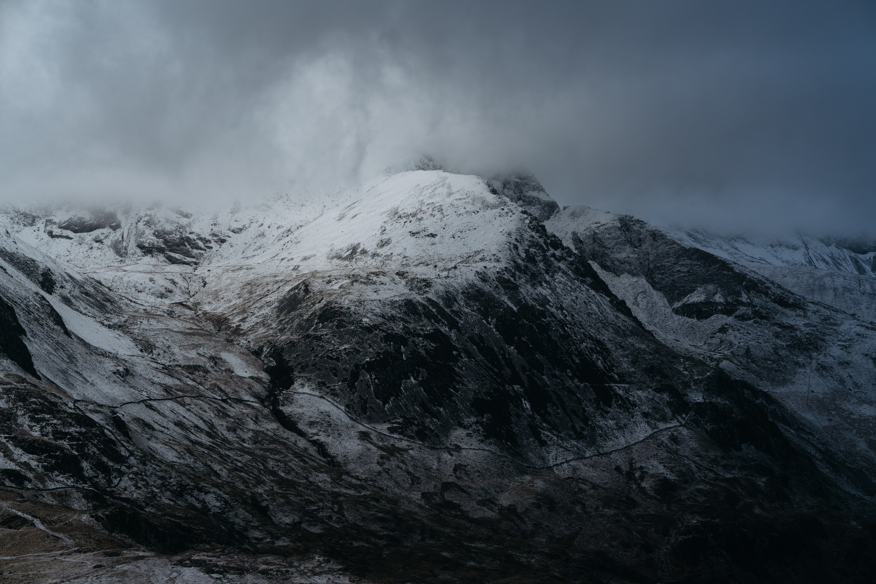A snow-coned mountain under a cloudy sky