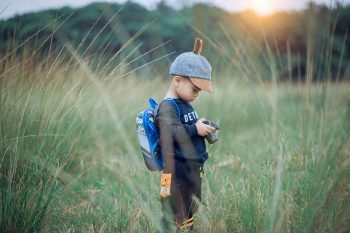 A toddler standing in the middle of the field holding a camera during sunset