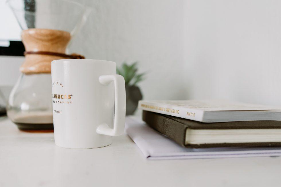A white mug standing near books on a white table