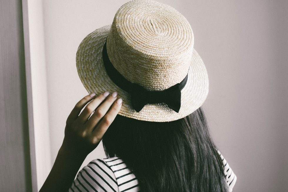 A woman holding a brown straw hat on her head