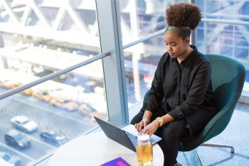 A woman in a black button-up top working on a MacBook