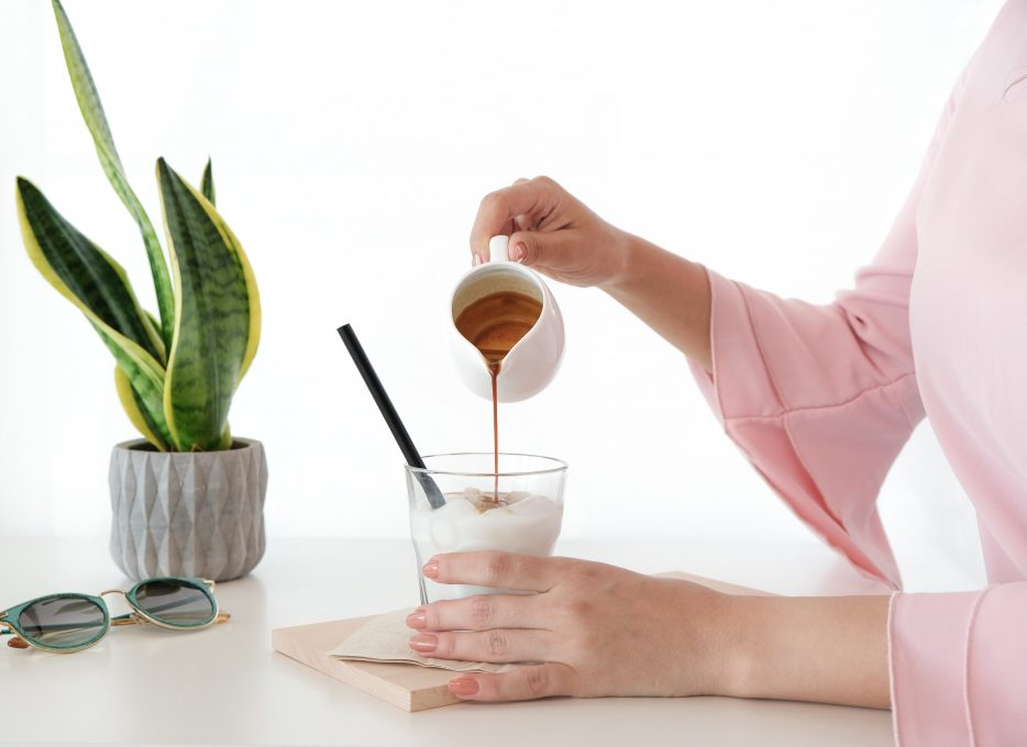 A woman pouring honey on a dessert
