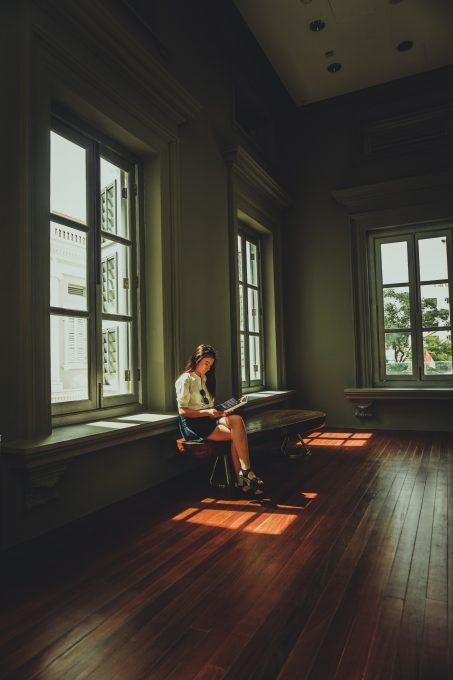 A woman sitting on a chair by a window reading a book