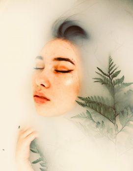 A woman taking a milk bath with a fern leaf