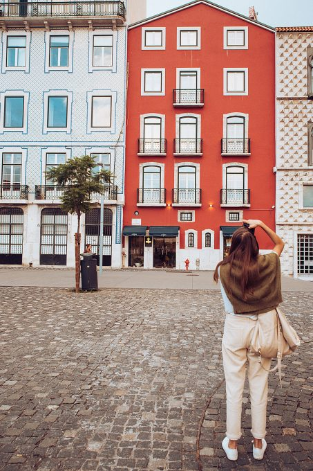 A woman taking photo of buildings
