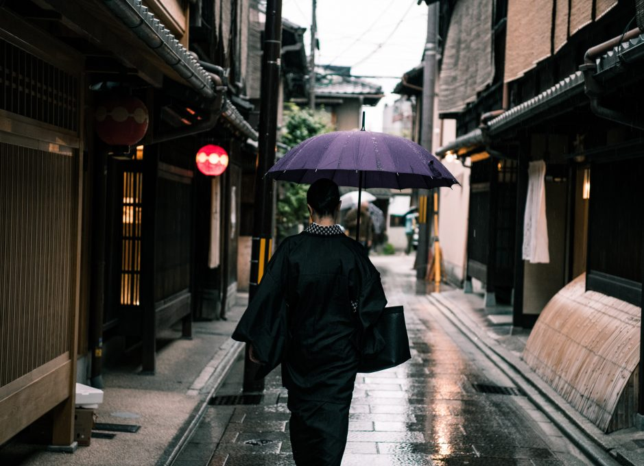A woman using a purple umbrella walking in the street