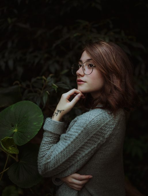 A woman wearing a black framed eyeglasses posing beside green plants