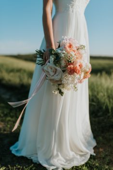 A woman wearing a white bridal gown while holding a bouquet flowers