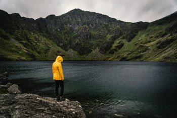 A woman wearing a yellow raincoat standing beside a river and mountain