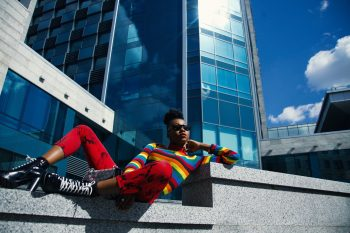 A woman wearing sunglasses sitting on a gray concrete fence near a building