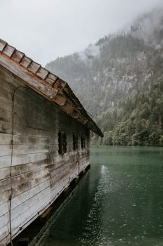 A wooden cabin surrounded by a body of water in front of foggy mountain