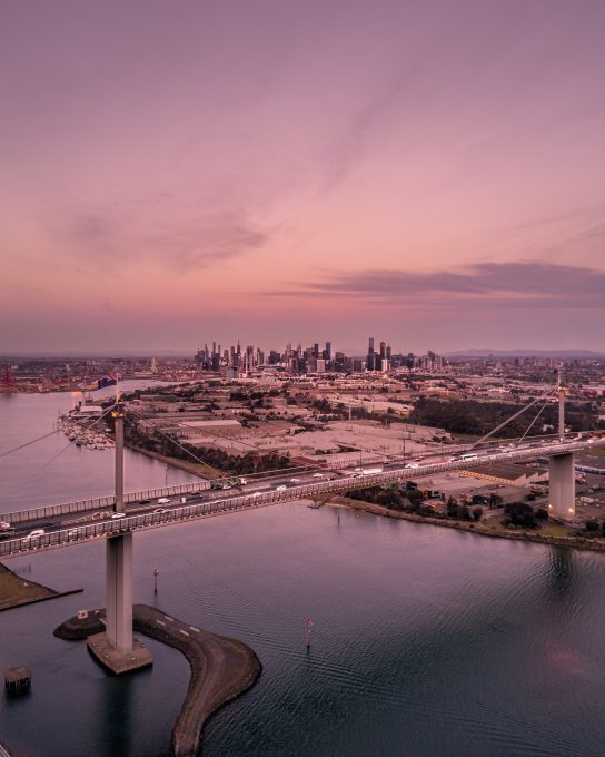 Aerial photography of city buildings and bridge during sunset