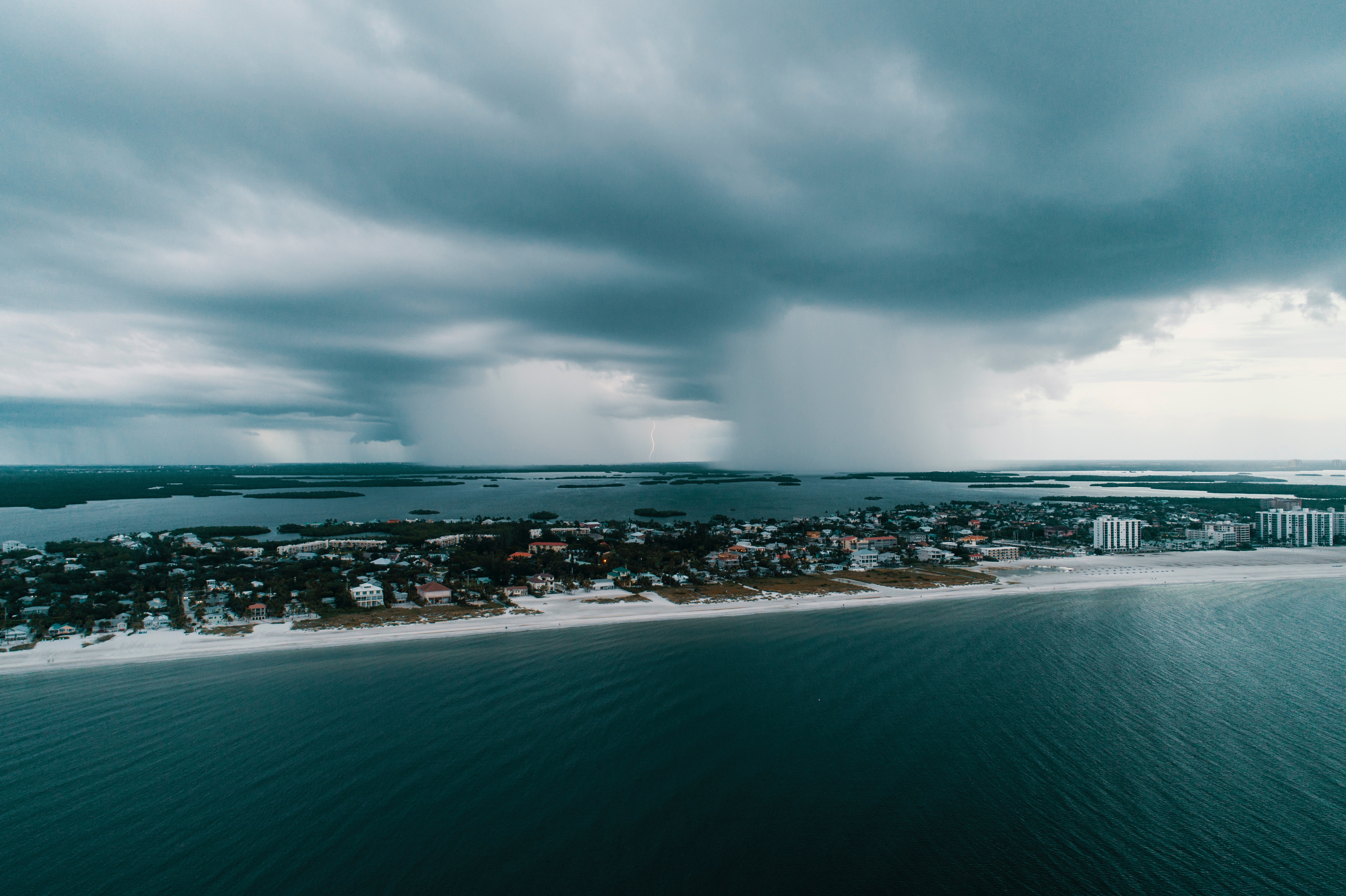 Aerial photography of city island under white clouds