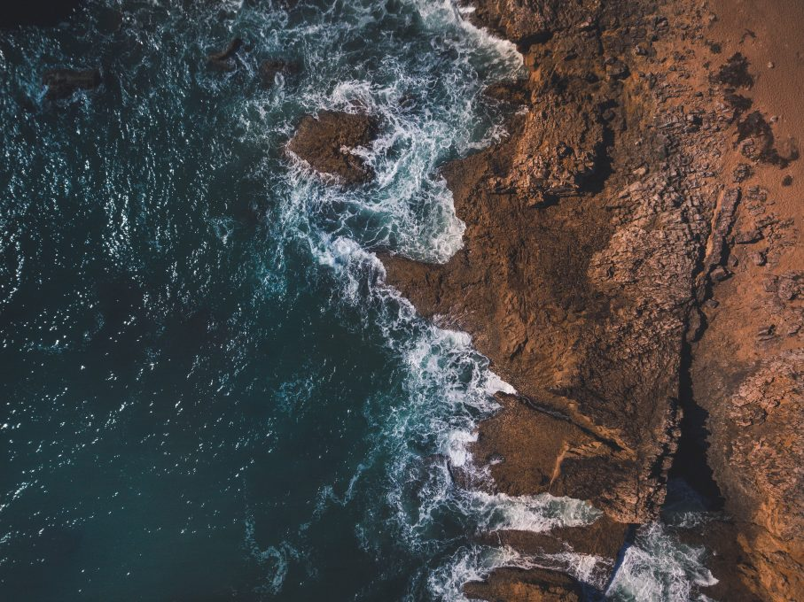 Aerial view of ocean waves and rocky coast