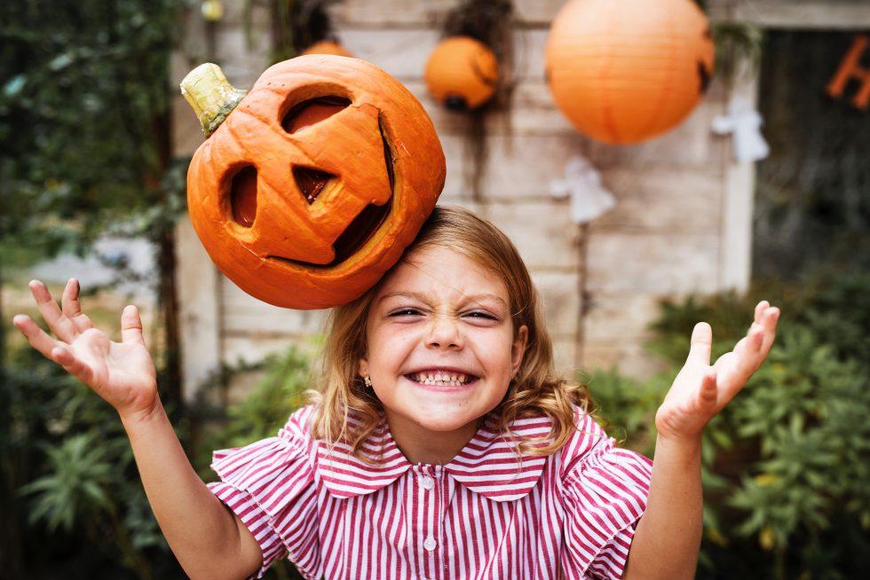 An orange pumpkin on girl's head
