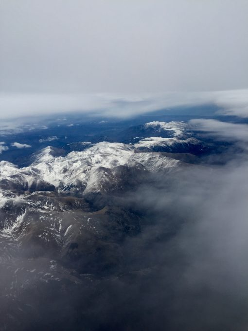 Bird eye's view of white mountains under clouds