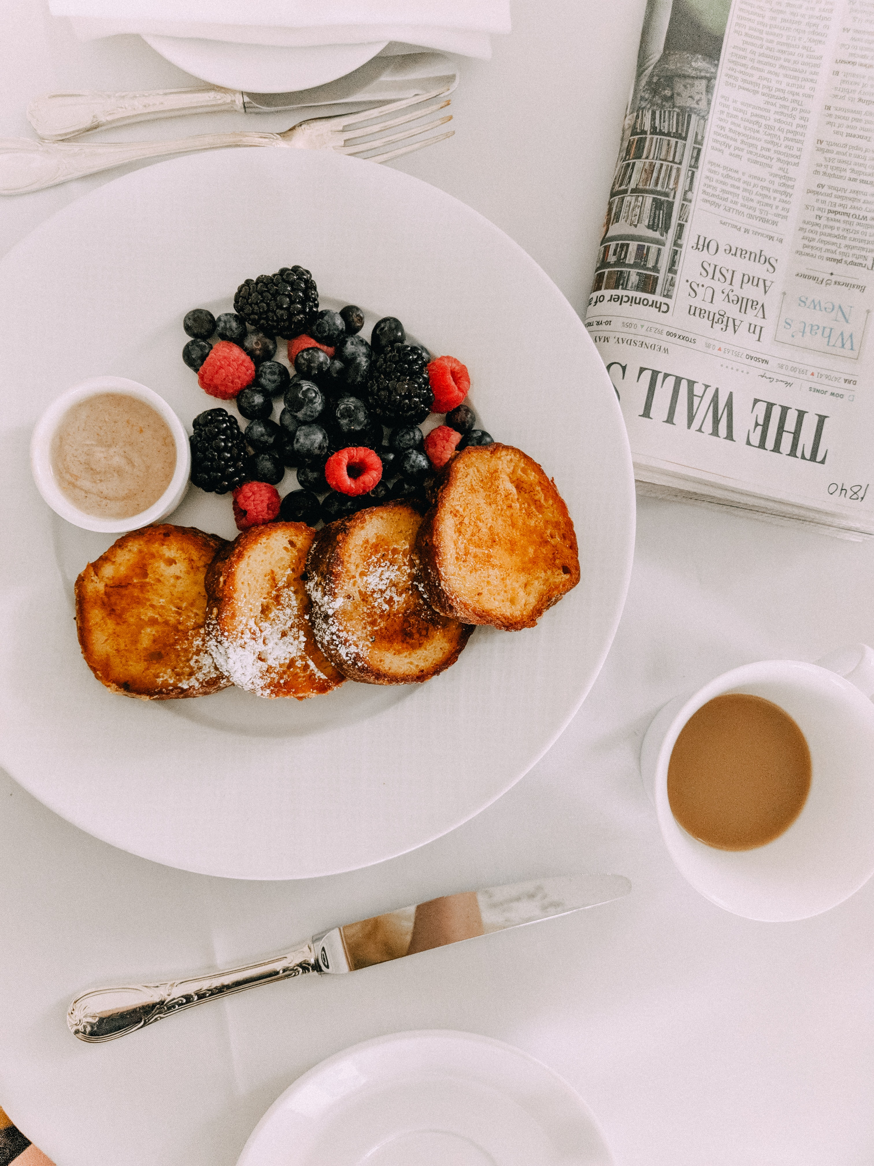 Breakfast with berries lying on a white plate on a white table
