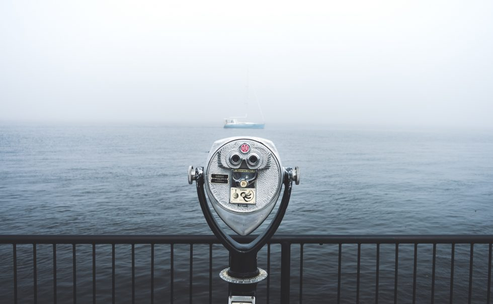 Coin operated binoculars looking over the ocean during foggy weather