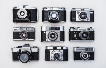 Flat lay photo of nine black-and-gray cameras