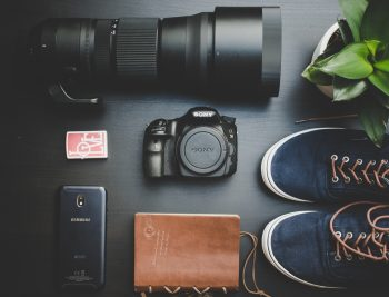 Flat lay photography of shoes near a camera and plant