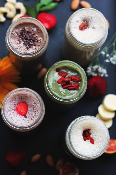 Flat lay with assorted-flavor milkshakes in glass jars