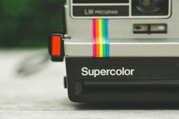 Gray and black Supercolor camera on a white surface