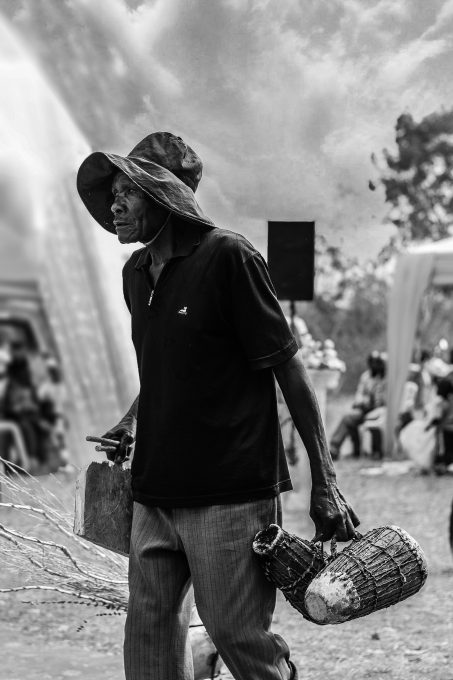 Grayscale photography of a man wearing a sun hat and carrying baskets