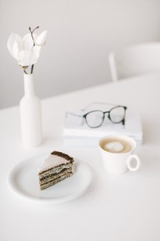 Minimalist photo of a cup of coffee and a slice of cake lying on a plate