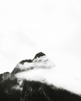 Monochrome photography of mountain under clouds