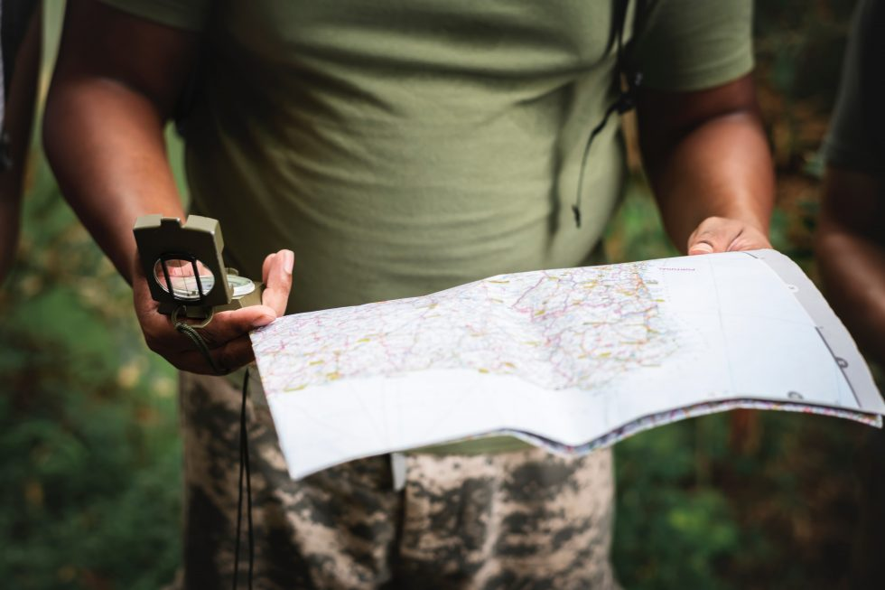 Photo of a person holding a map and compass
