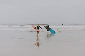 Photography of people on seashore holding surfboards during the fog