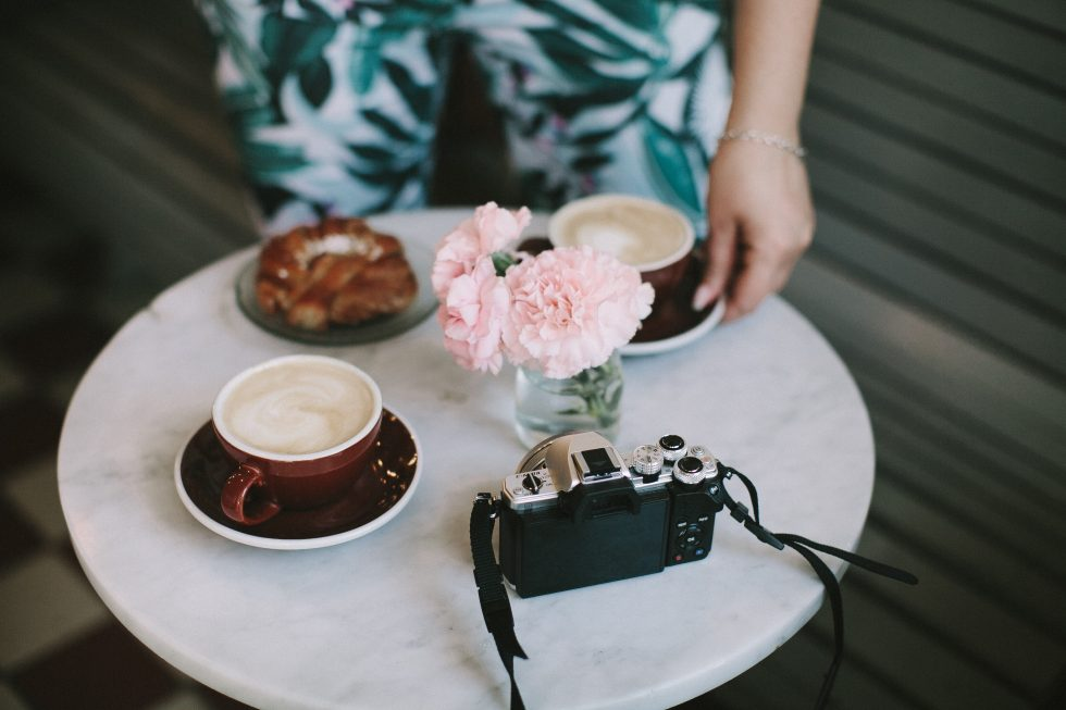 Pink flowers in a glass jar near and a cup of coffee a camera
