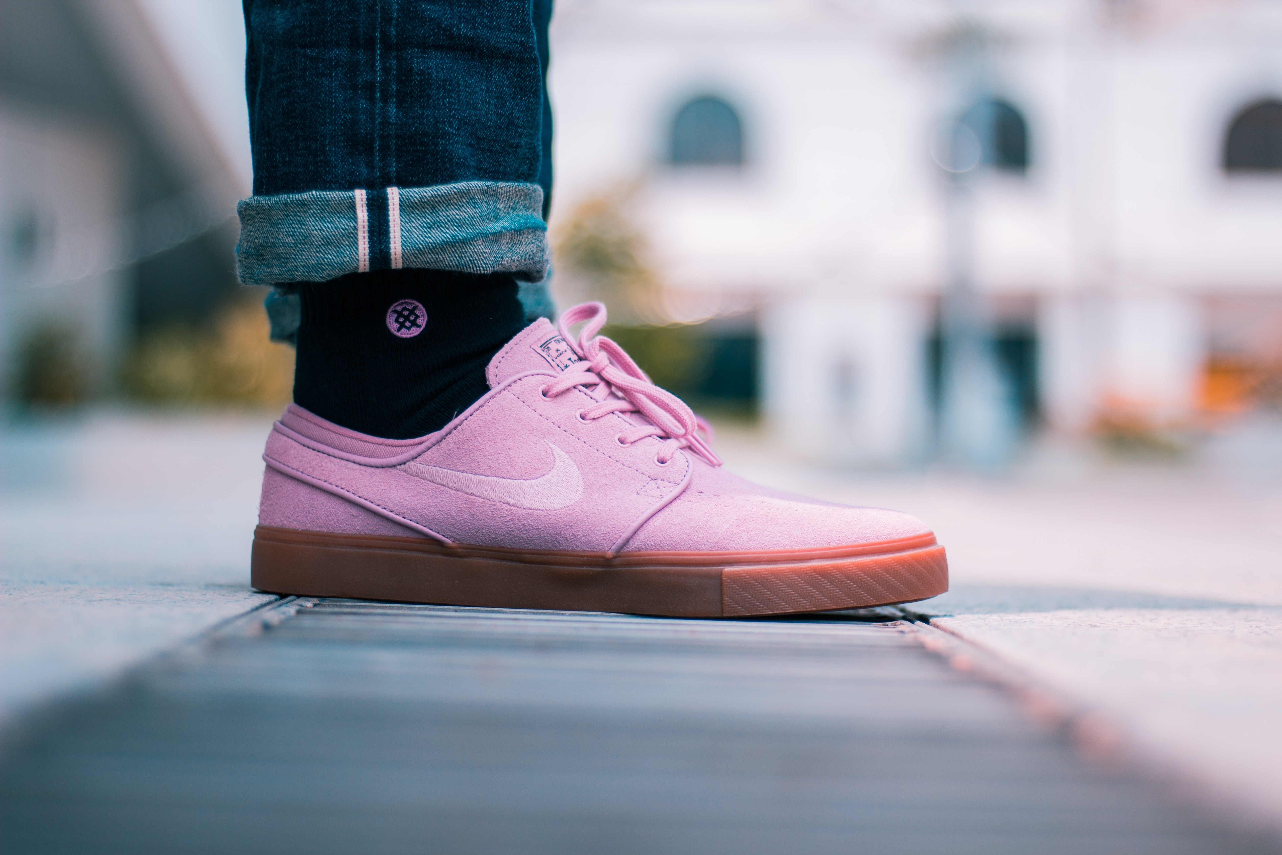 Selective focus photo of a person wearing pink Nike low-top sneakers