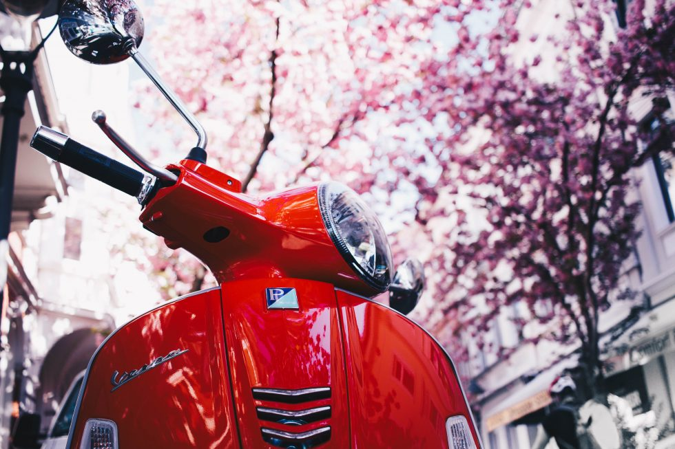 Selective focus photography of a red motor scooter under blooming trees