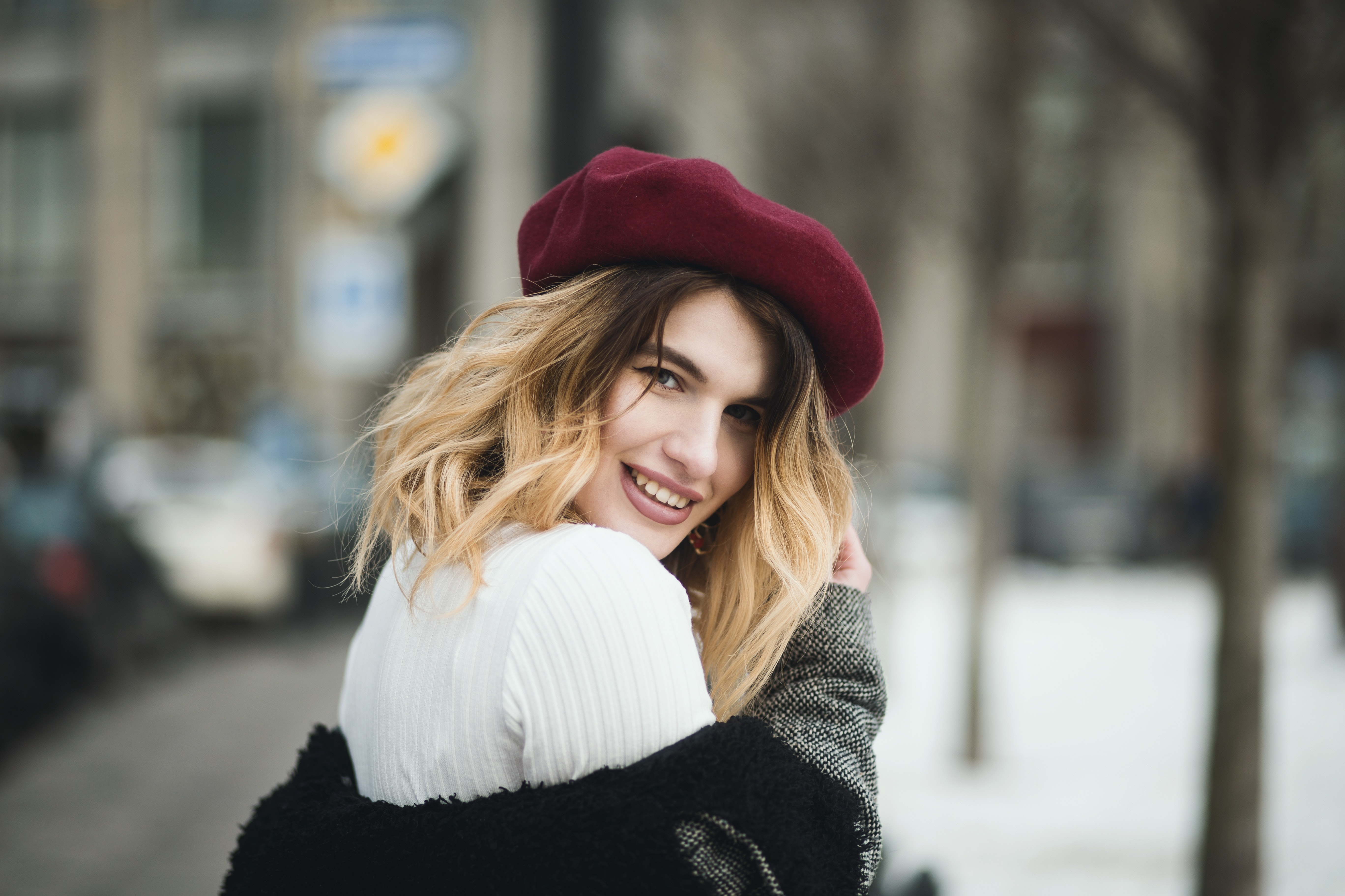 Selective focus photography of a smiling woman wearing a red hat