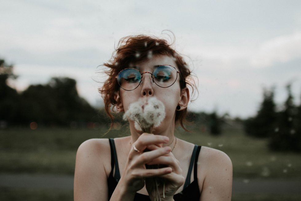 Selective focus photography of a woman blowing dandelion flowers