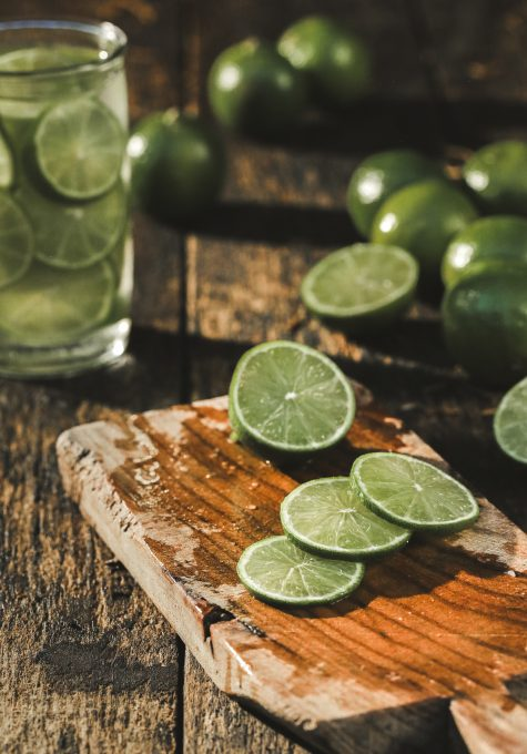Slices of limes on a brown wood chopper