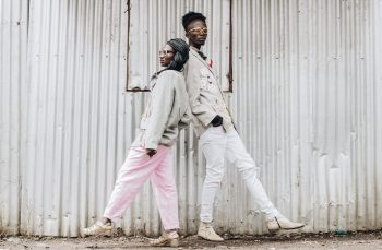 Stylish man and woman standing back to back