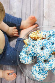 Top view of doughnuts in a glass plate beside a child