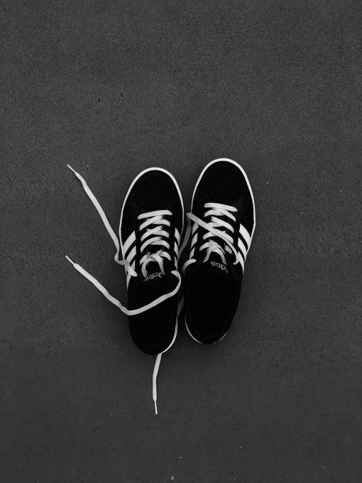 Top view of pair of black-and-white Adidas sneakers on the gray floor