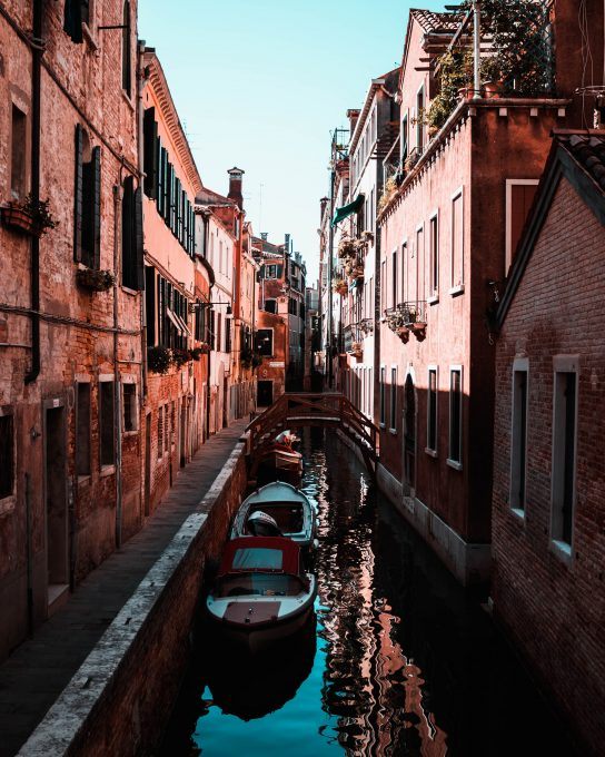 Two boats floating on the water between buildings